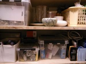 Alemmalla hyllyllä vasemmalta oikealle: kynttilät, patterit ja polttimot yms, varalamput, palohälyttimet ja takana jatkojohdot omassa korissaan. Ylähyllyllä on laatikossa lannoitteita, koristekiviä yms ja niiden vieressä maljakoita ja ruukkuja.